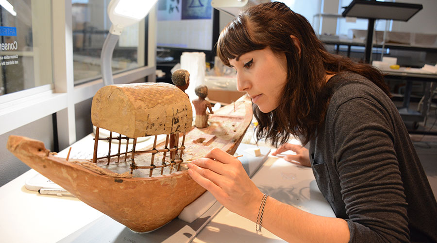 Conservator working on Boar object