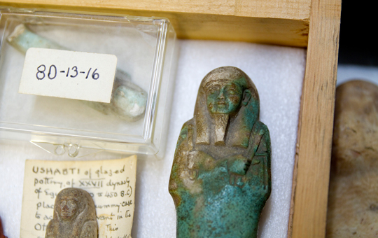 Small Egyptian artifacts in a storage box