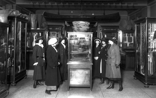 a group of women looking at objects in a display case