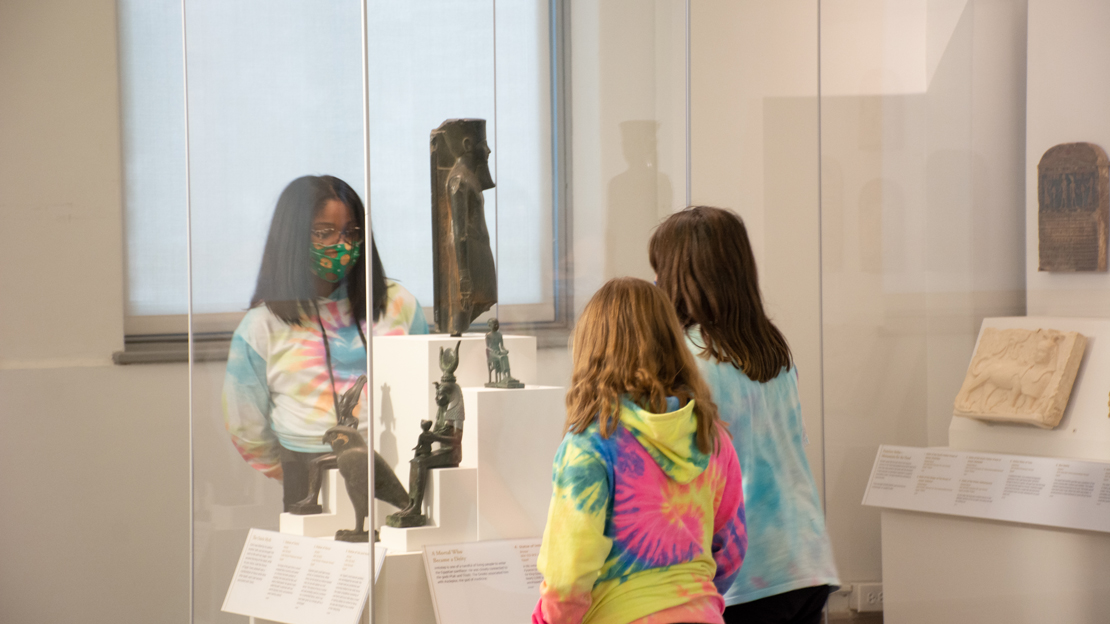 Three children wearing masks and looking at an artifact in the gallery.