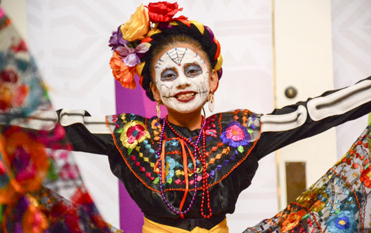 A girl with face paint and traditional outfit performing a dance.