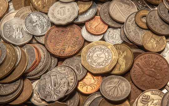 A pile of coins of all shapes and sizes from different countries.