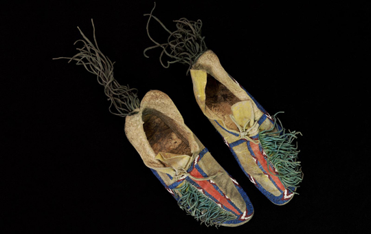 Beaded moccasins with tassels.