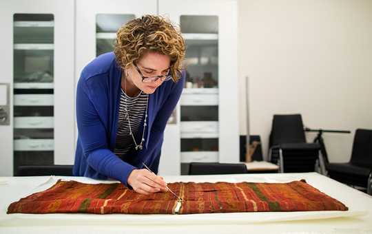 Anne Tiballi working with ancient textiles in a lab