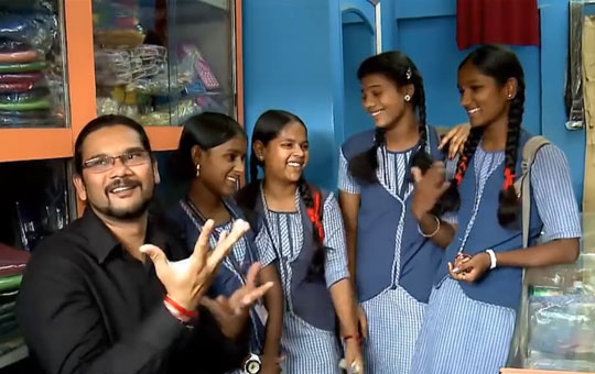A man and four school girls having a conversation with lots of gestures