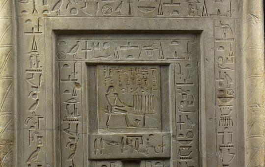 A stone door covered in Egyptian hieroglyphs.