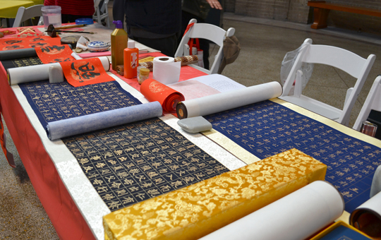 Table covered in scrolls with Chinese characters.