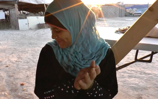 A woman in a headscarf, her hands clasped.