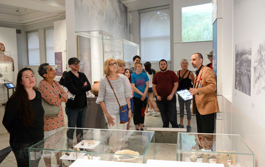 tour group learning in a gallery from a global guide