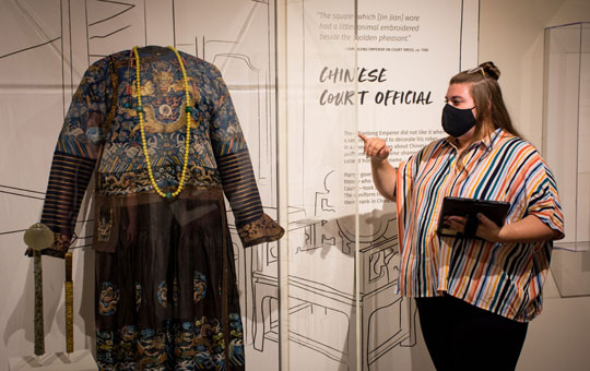 A Graduate Guide giving a tour in the Stories We Wear exhibit.