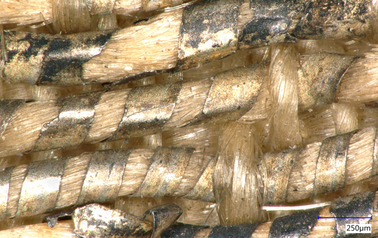 Close up of woven threads wrapped in metal