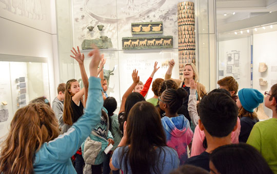 A school group in the Middle East Galleries, with hands raised to ask a guide questions.