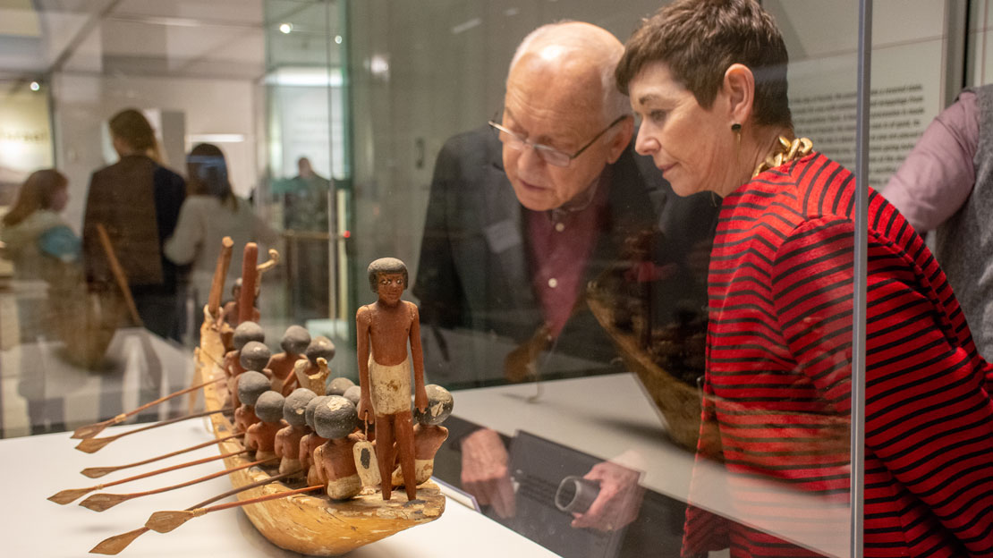 a couple looking at an ancient Egyptian artifact of a boat