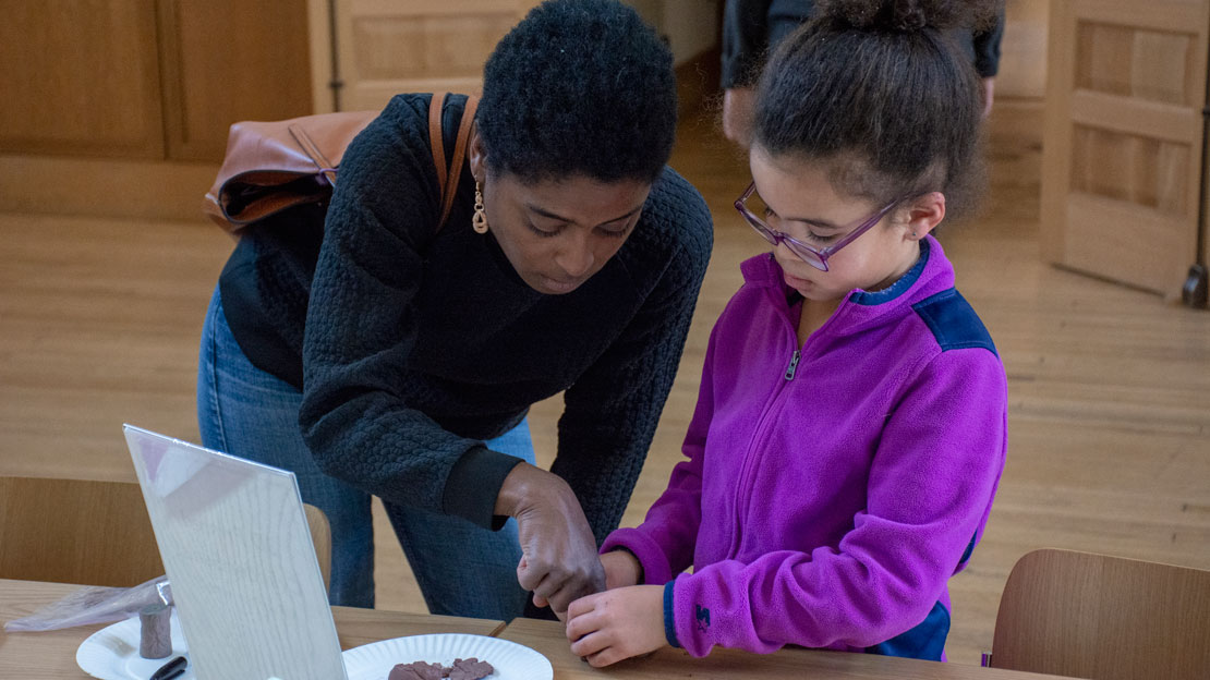 A mother and daughter working on a museum craft together.