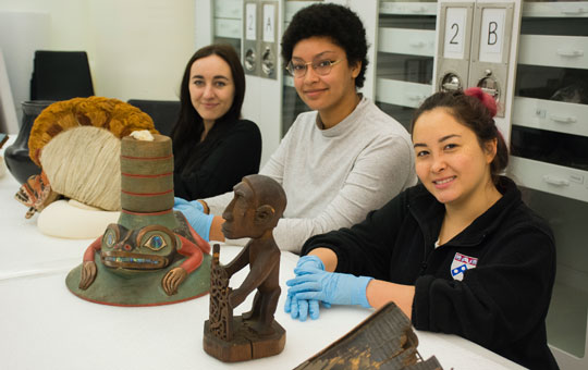 Three students posing with artifacts in a lab.