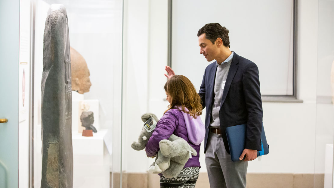 A father and daughter discussing an artifact in a case.