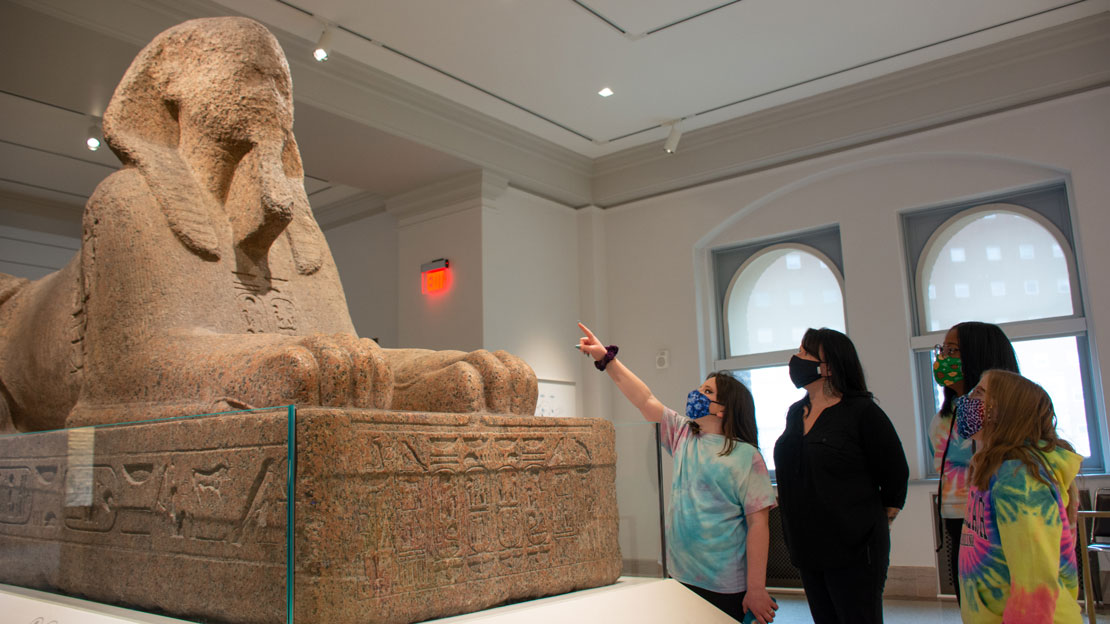 A group of children with a chaperone, wearing masks and pointing to the Sphinx.