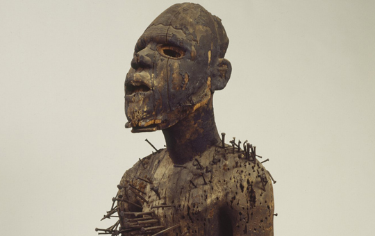 Wooden figure of a man with nails driven into the body.