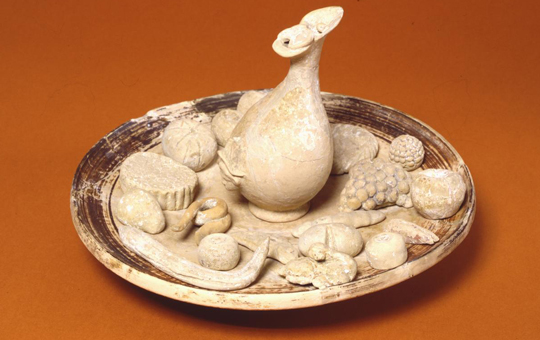 Ceramic offering depicting a platter of food and a pitcher.