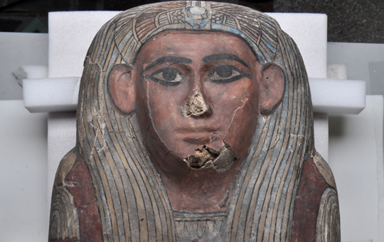 The head and shoulders of a painted sarcophagus.