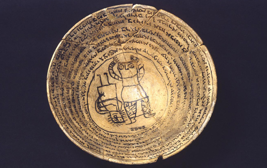 An incantation bowl with two figures in the middle and inscriptions around the inside.