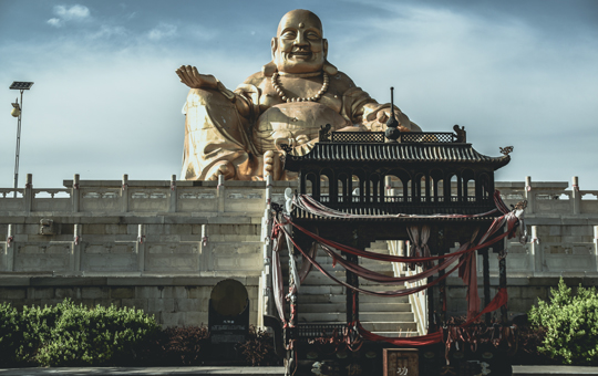 A monumental statue of the Buddha in the background of a Buddhist temple