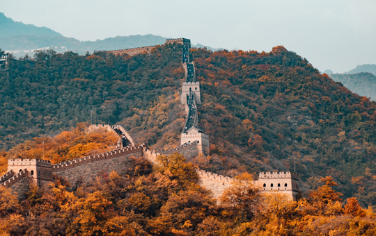 A view of the Great Wall of China with trees changing to fall colors surrounding