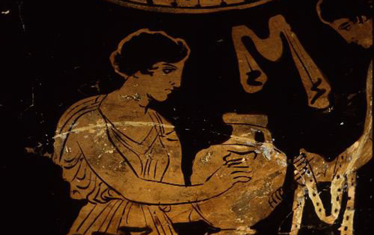 Close up of a decoration of a greek vase showing a woman holding a vessel