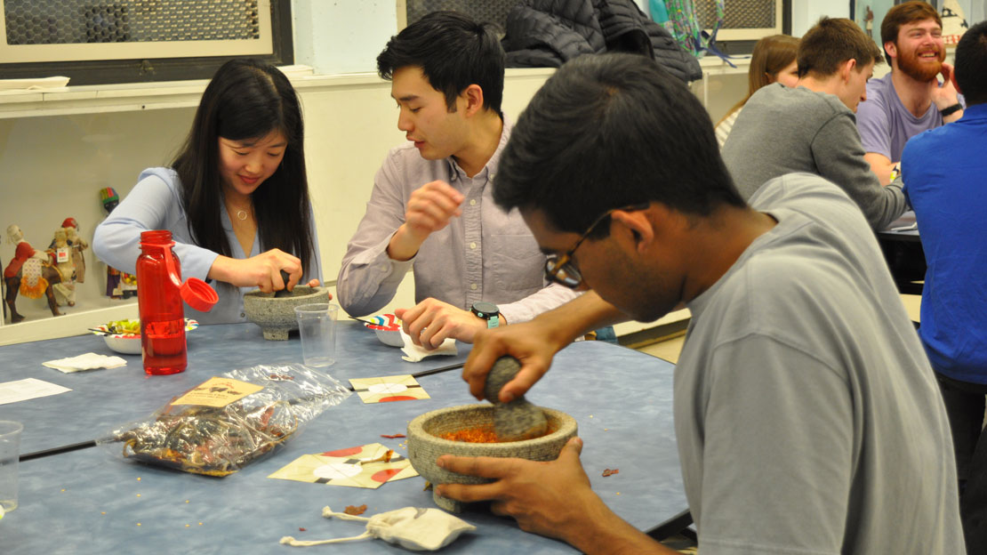 students making salsa with a mortar and pestle