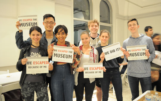 students holding 'we escaped the museum' signs