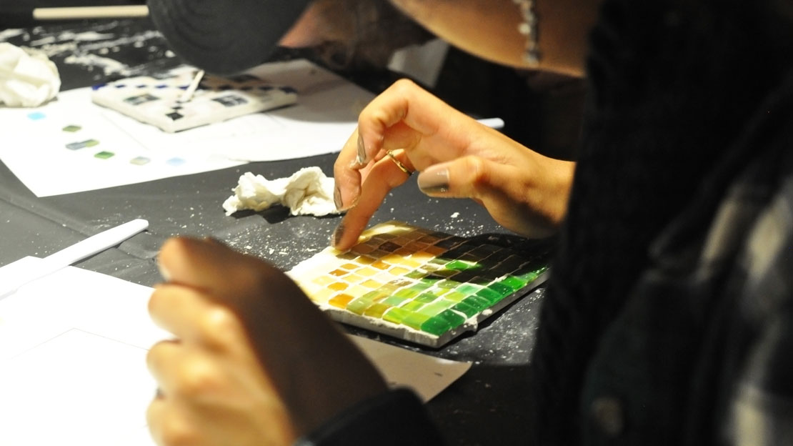 close up of a student carefully placing pieces of a mosaic