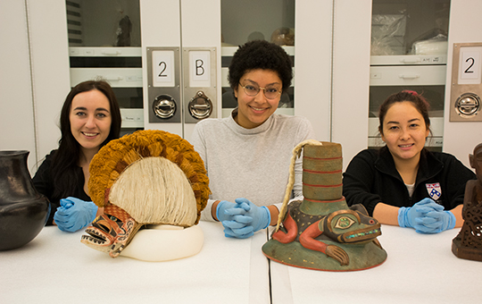 students posing with artifacts