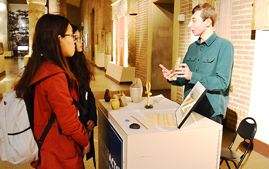 students learning about an artifact at a booth