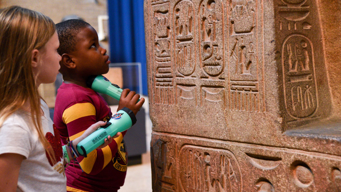 children examining closely hieroglyphs