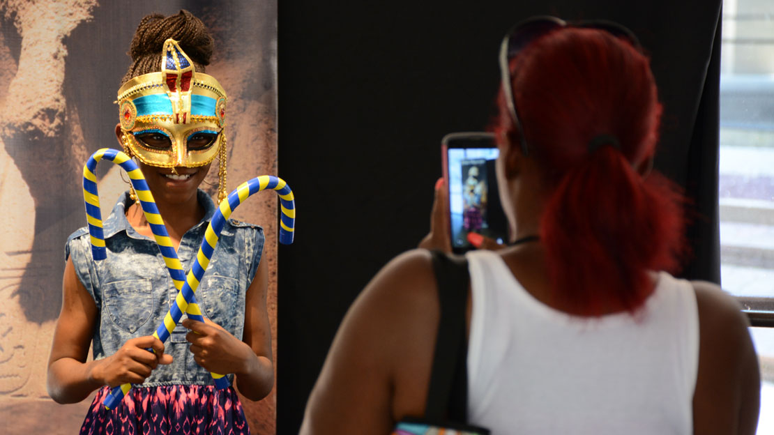 a mother taking a picture of her daughter dressed up like a pharaoh