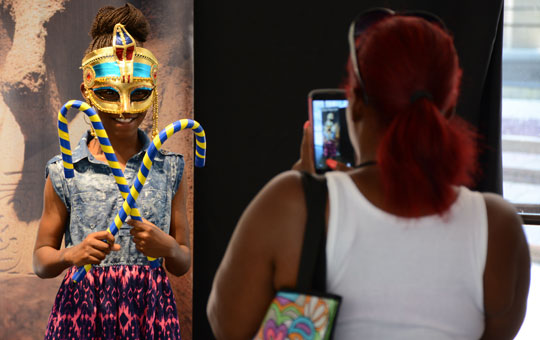 a mother taking a picture of her child dressed up like a pharoah