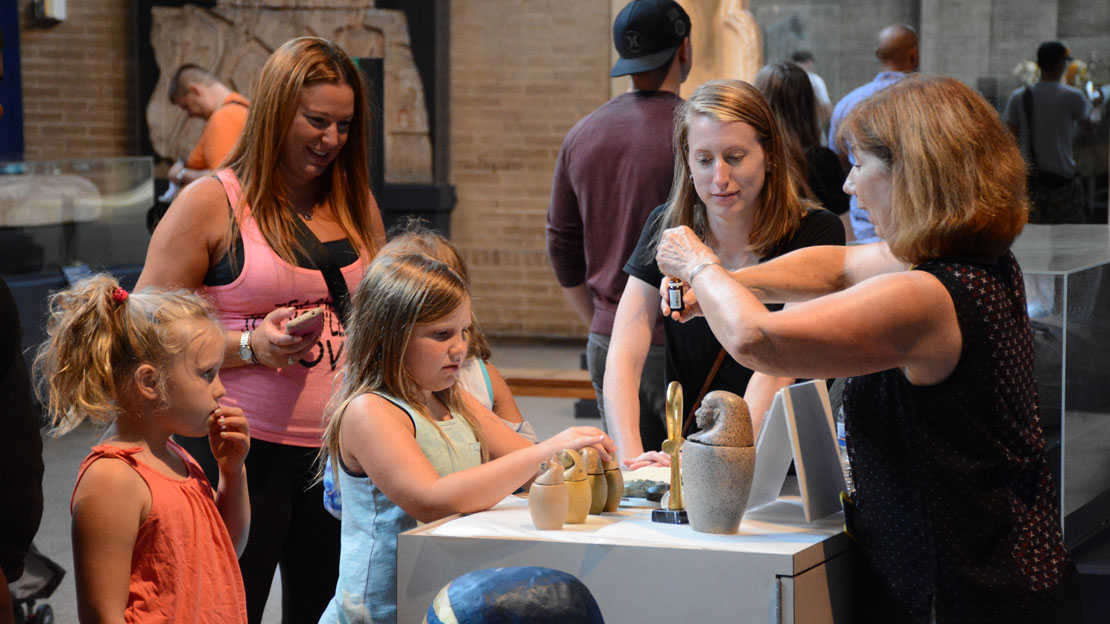 a family watching a demonstration about a museum artifact