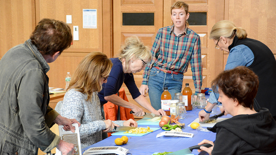 As part of an herbology course, an instructor stands above a table with 5 people cutting various vegetables.