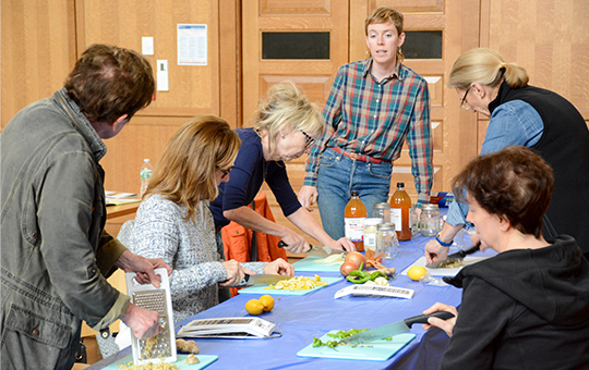As part of an herbology course, an instructor stands at the head of a table of 5 people cutting up various vegetables