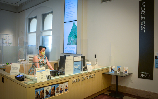 The ticketing desk in the Sphinx Gallery, with a staff member wearing a mask.