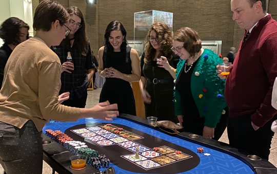 A group gathered around a casino table playing a game